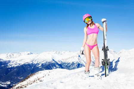 Beautiful young girl in pink bikini and helmet standing on the top of the mountain with skies Stockfoto