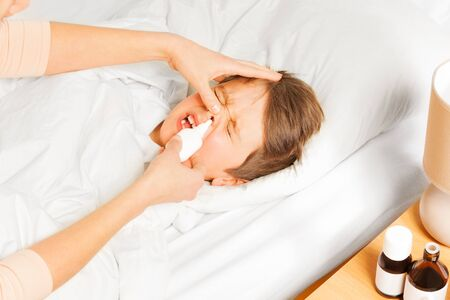 snivel: Sick five years old boy laying in bed and crying while mother spraying him nasal spray or drops in nose