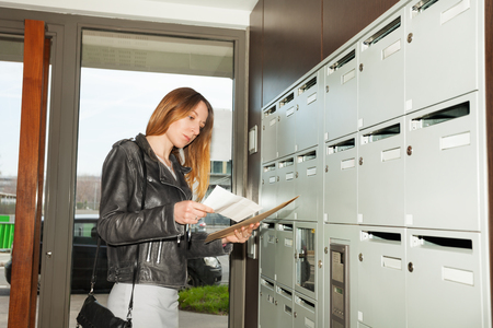 Portrait of pretty woman checking junk mail standing at the hall Stock Photo