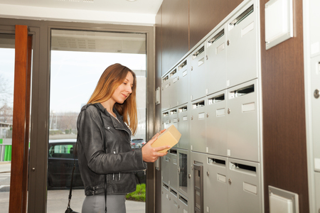 addressee: Happy young woman holding parcel in her hands standing next to mailboxes