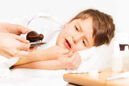 Sick kid boy laying in bed and crying while mother pouring coughing syrup from bottle with copy-space to metering spoon Standard-Bild