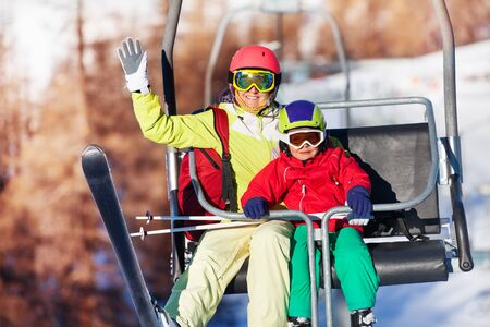 kids at the ski lift: Happy skiers lifting on chairlift at mountains Stock Photo