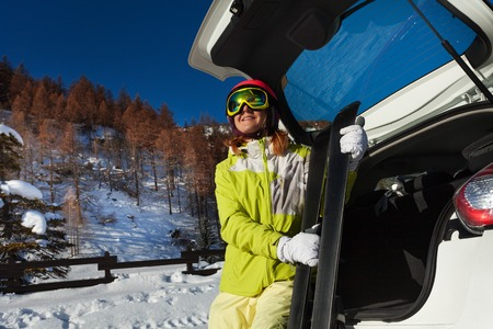 Happy woman sitting in car trunk and holding skis