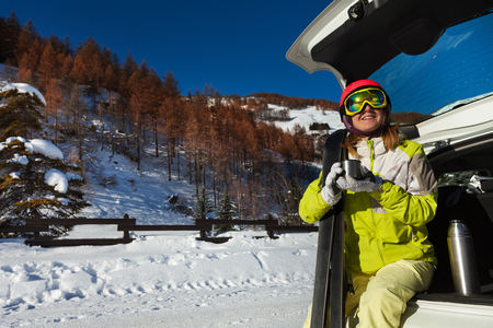 Woman having rest after skiing and drinking tea