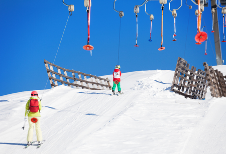 Active family lifting on button lift at sunny day Stock Photo