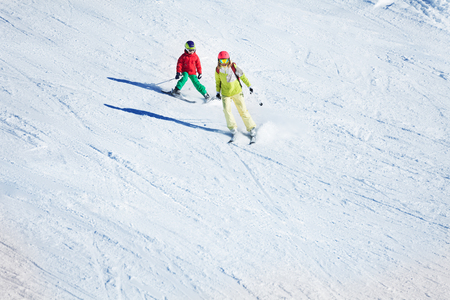 Two skiers hitting the slopes at snowy mountains