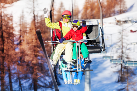 kids at the ski lift: Happy skiers lifting on chairlift and waving hands Stock Photo