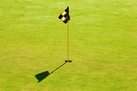 Hole and flag above putting green on golf course Stock Photo