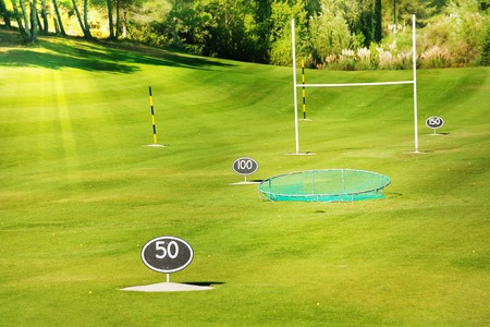 Driving range at golf course with yard signs