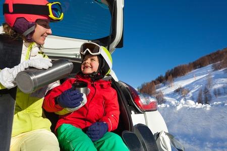Gelukkige moeder gieten thee voor haar zoon na het skiën Stockfoto