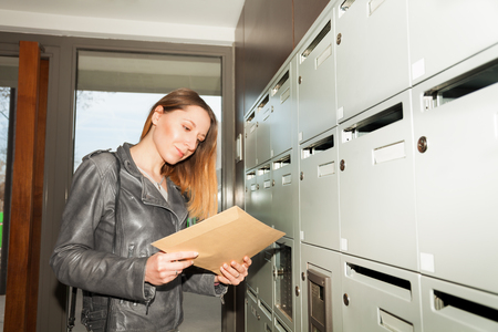 addressee: Woman holding envelope standing next to mailboxes Stock Photo