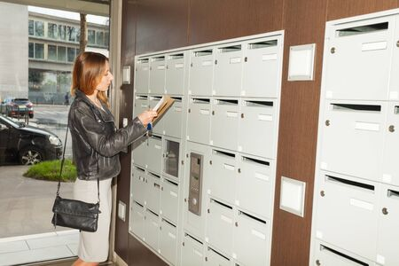 addressee: Young woman taking mail out the mailbox