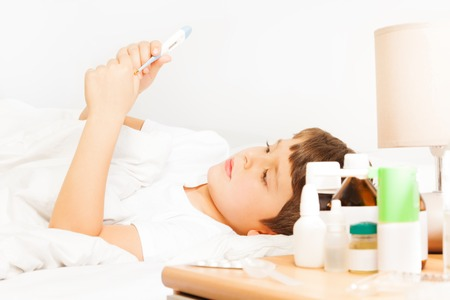 Boy checking thermometer readings laying at bed