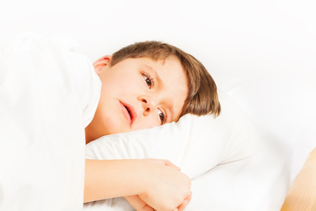 Sad boy laying in bed on white background Stock Photo