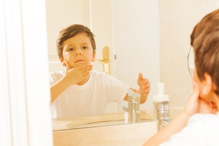 miror: Kid boy washing his face and looking in the miror Stock Photo