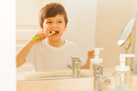 bathroom mirror: Reflection of boy in mirror during tooth brushing
