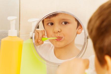Leuke jongen die in de glas en het borstelen tanden kijkt Stockfoto