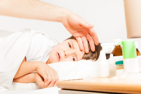 Boy crying while father measuring his temperature Stock Photo