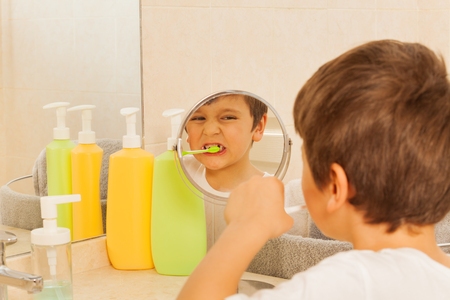 Boy looking in the glass during tooth brushing