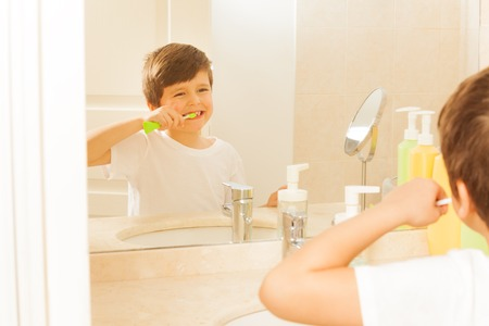 Boy brushing teeth and looking at mirror in bath