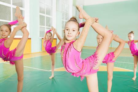 Gruppe von sechs Gymnastikmädchen, die sich in der Turnhalle strecken Standard-Bild - 77917825