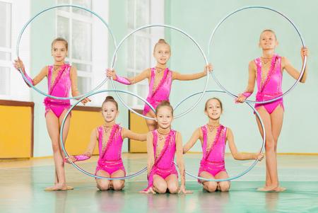 Gymnast meisjes met hoepels poseren in de sportschool