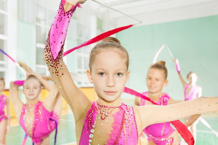 Little girl perform gymnast exercise in group