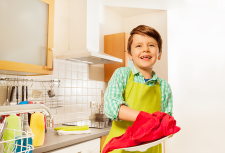 clout: Happy kid boy wiping dry plate with red dish towel