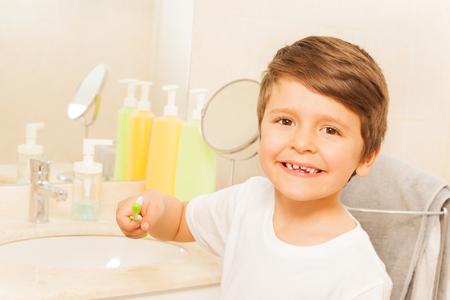 Happy kid boy brushing teeth in the bathroom Stock Photo