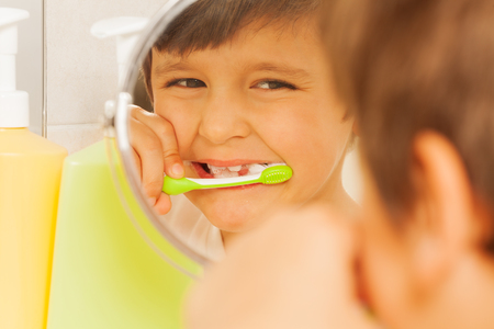Boy looking in glass and learning to brush teeth