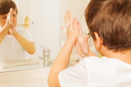 Boy washing hands with soap and looking in mirror Stock Photo