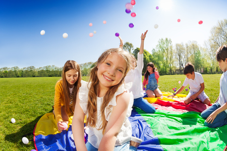 Smiling girl playing with friends in the park Stock Photo