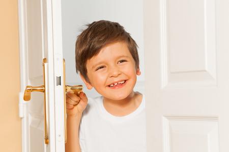 Happy kid boy looking through the doorway