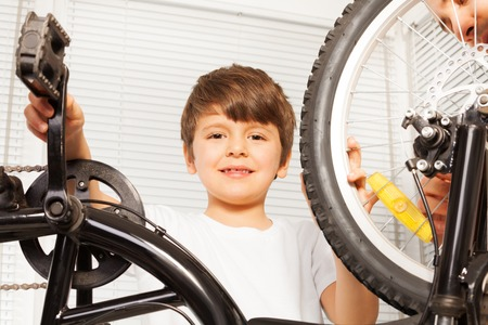 Smiling six years old boy repairing his bicycle Stock Photo