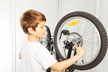 Kid boy repairing his bicycle at garage