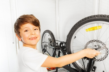 Happy boy repairing his bicycle wheel with spanner