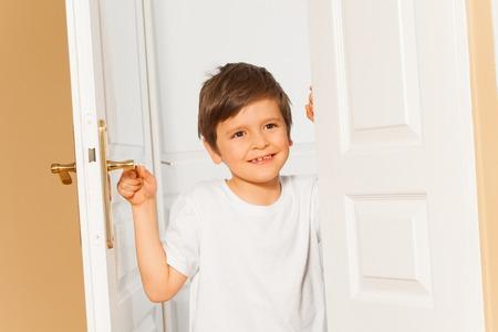 집에서 흰색 문을 여는 웃는 아이 소년