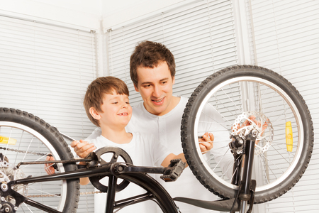 Dad showing his kid son how to repair bicycle Stock Photo