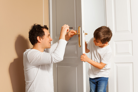 Father teaching his son to repair the door handle Stock Photo