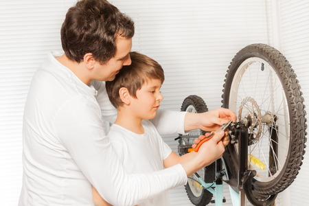 Father repairing brakes of bicycle with his  son