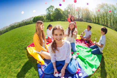 Meisjeszitting op groen gazon die kleurrijke ballen houden