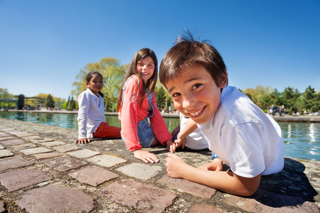 Cute boy sitting on the embankment with friends Stock Photo