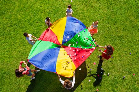 Gelukkige kinderen wapperende regenboog parachute vol met ballen