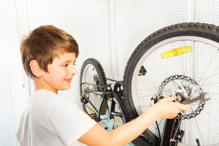 Boy using a spanner while repairing his bicycle
