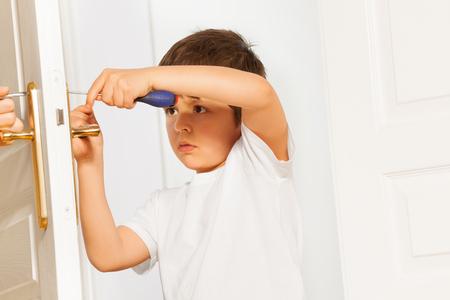 Little helper fixing door handle using screwdriver Stock Photo