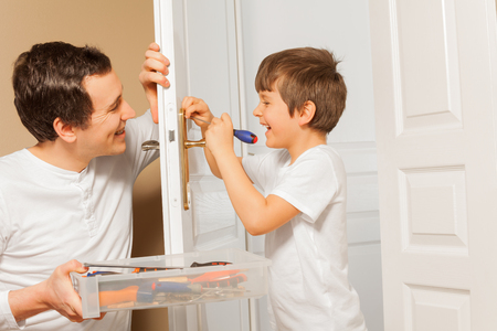 Man helping his son to draw up bolt of door handle