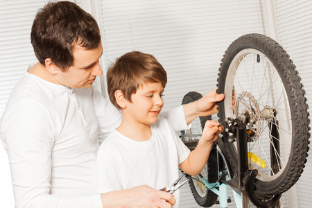 Father with son replacing cable in bicycle brakes