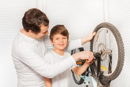 그의 아버지가 자전거 브레이크를 수리하는 것을 도와주는 소년 스톡 콘텐츠