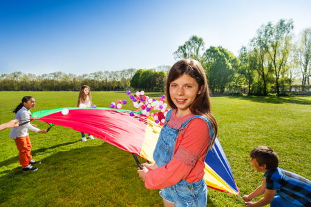Girl playing parachute game on the green field Stock Photo