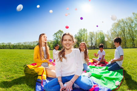 Girl throwing colorful balls playing with friends 스톡 콘텐츠
